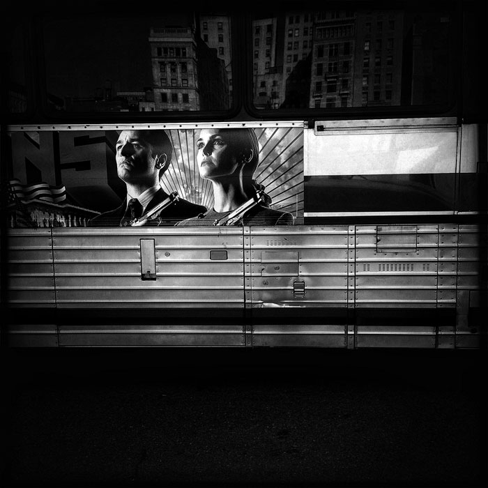Advertising on NYC City bus  showing heros with guns.